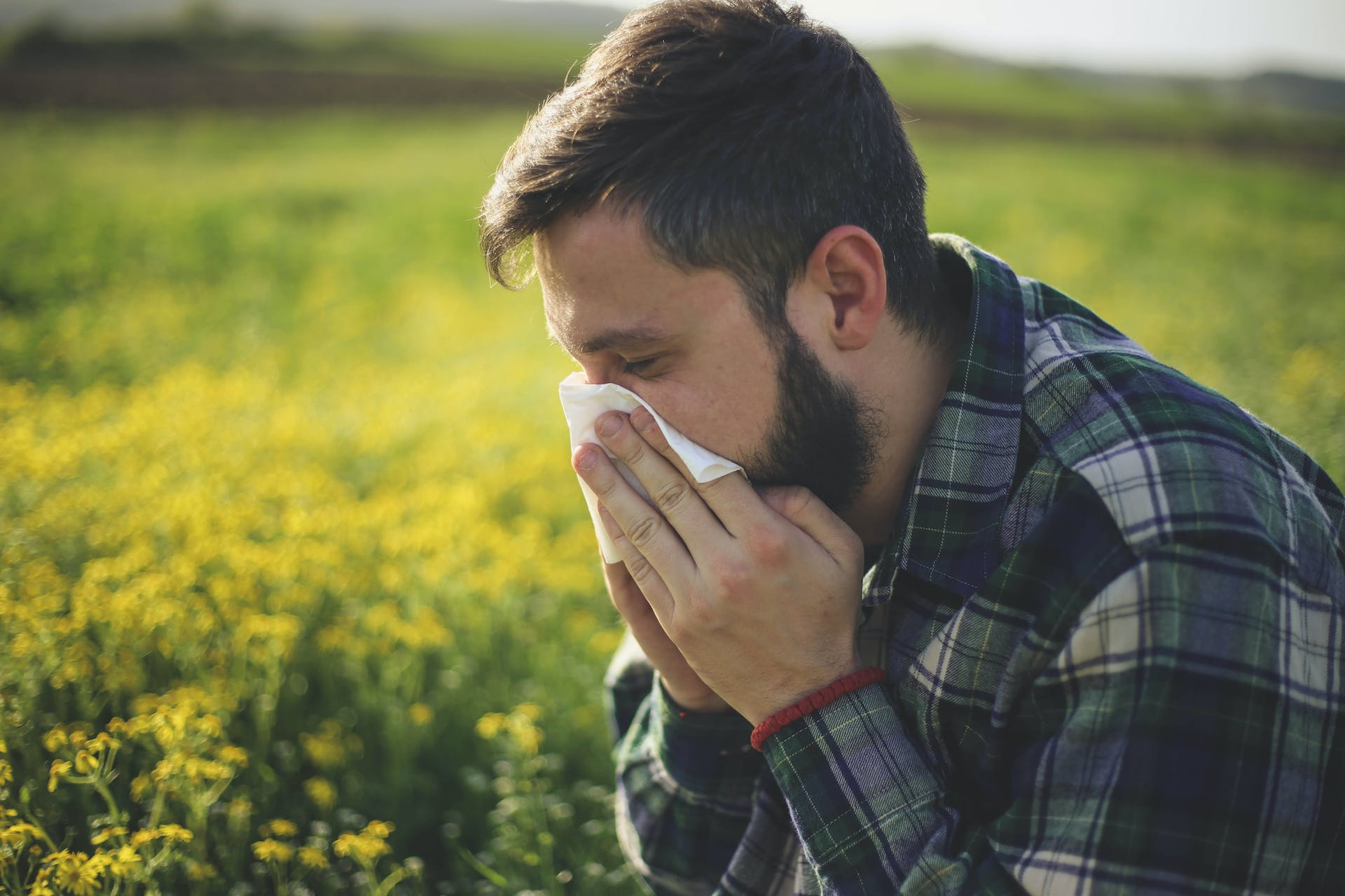 A man sneezing with allergies